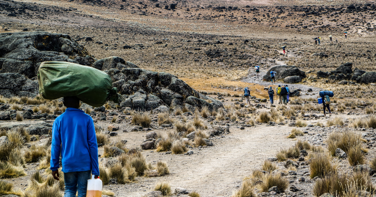 Porters carrying bags on route to Kilimanjaro summit.