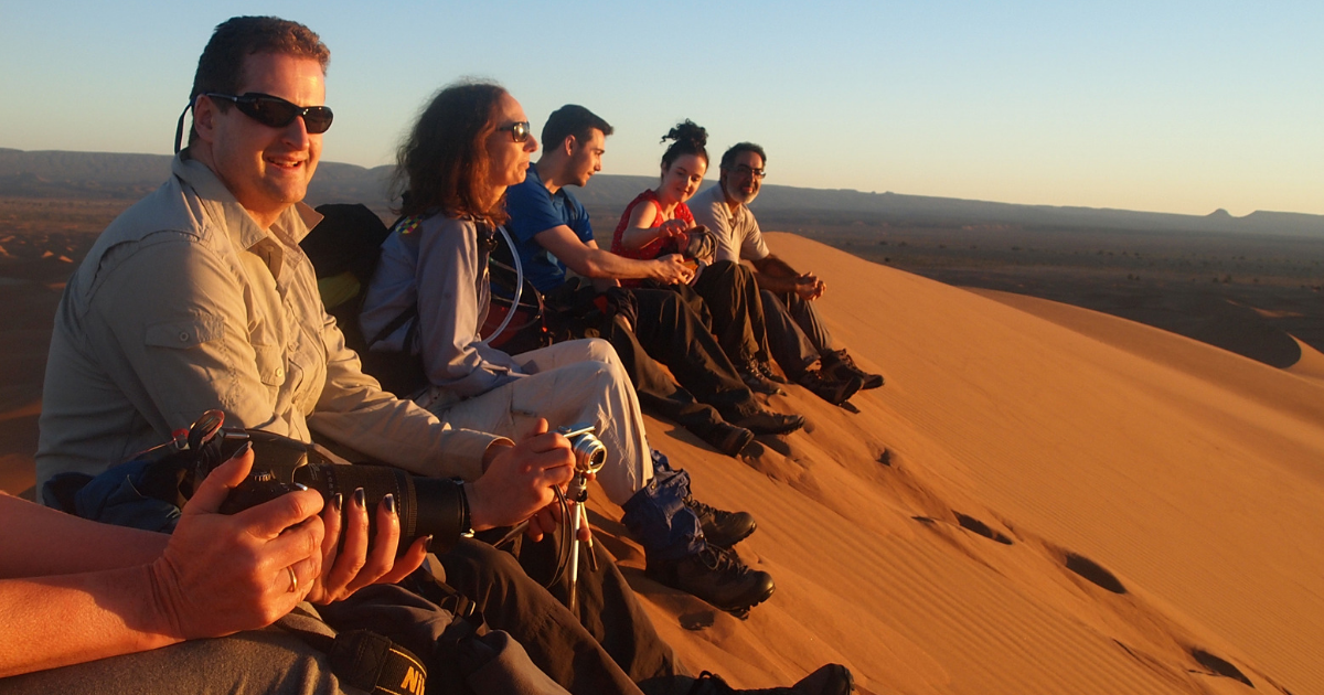 People look out over the Sahara Desert