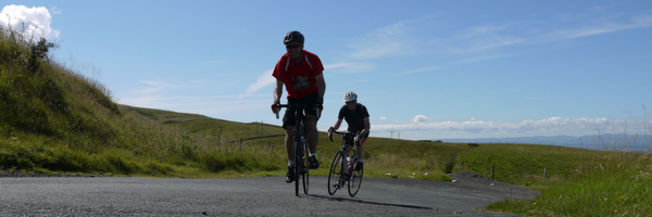 Two people taking on a cycling challenge